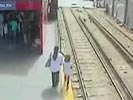 Mother drops girl on the train track seconds before a train comes.